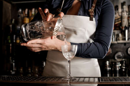 Female professional barman pouring fresh summer drink into an elegant cocktail glass on the dark bar counter Stock Photo