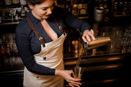 Lovely sexy smiling barmaid with a deep neckline making a fresh summer cocktail in a shaker Stock Photo