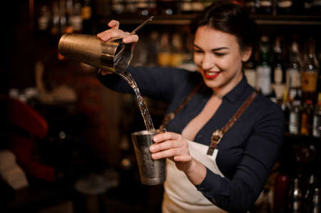 Beautiful sexy smiling barmaid with a deep neckline making a fresh summer cocktail in a shaker Stock Photo