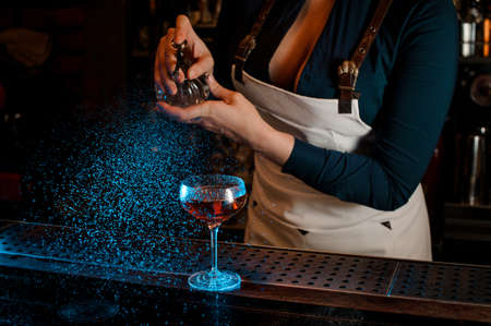 Sexy female barman with deep neckline spraying blue-colored bitter on the elegant cocktail glass on the bar counter 版權商用圖片