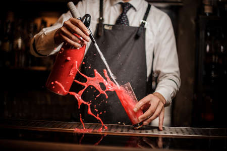 Barman pouring alcoholic sparkling water into a sweet red berry summer cocktail and splashing around on the bar counter