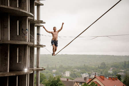 Brave man balancing on a slackline high against empty building and sky on rainy summer day