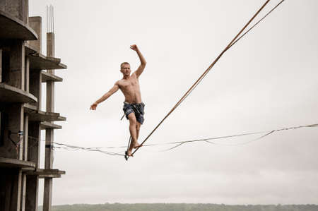 Fearless man balancing on a slackline high against empty building and sky on rainy summer day Banque d'images