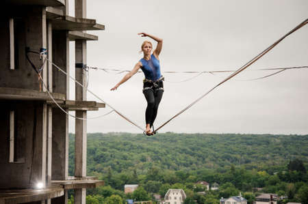 Strong woman balancing on a slackline against the background of high empty building on summer day