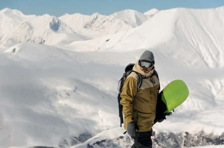 guy in ski equipment and glasses is holding a green snowboard on the background against the snowy mountains