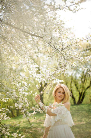 Vertical romantic portrait of happy blonde woman in white dress near the blooming cherry tree