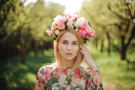 Beautiful blonde woman dressed in a flower dress and pink wreath on her head standing on the background of green forest Archivio Fotografico