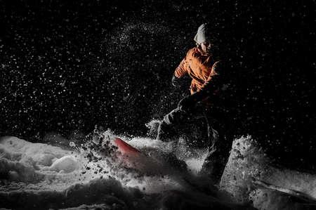 Young man riding on the snowboard in the mountain in the night in the poplar tourist resort in Gudauri, Georgia Stock Photo