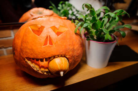Halloween horror ball orange pumkin with the light inside with the small pumkin in the mouth near the green plant in the white pot Stock Photo