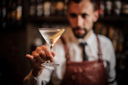 Bartender in the white shirt and brown leather apron holding a transparent cocktail in the martini glass on the bar counter on focus Фото со стока
