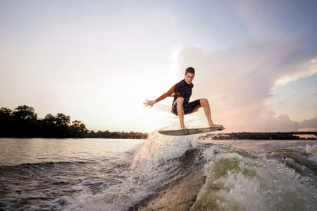 Young attractive man jumping on the wakeboard on high wave of motorboat on the background of lakeside and bridge