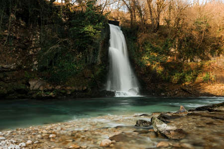 Beautiful waterfall flowing into clear river in Martvili canyon on autumn day