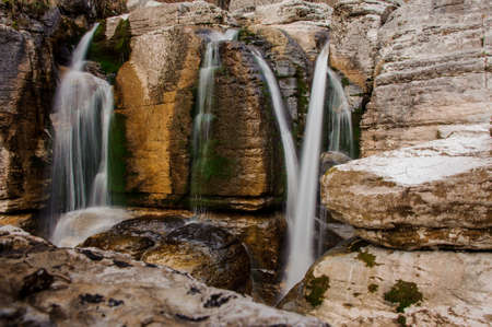 Several waterfalls flowing down the high rock with moss in Martvili canyon on autumn day Фото со стока