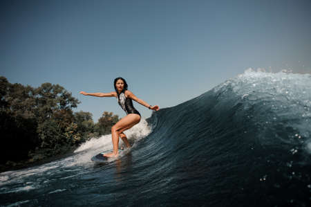 Sexy slim brunette woman wakesurfing on a board down the blue water on sunny day