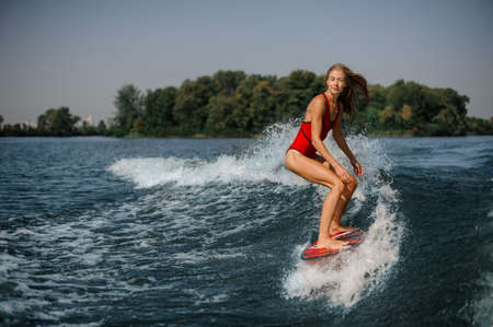Beautiful blonde girl in the red swimsuit standing on the red wakeboard on the bending knees Zdjęcie Seryjne