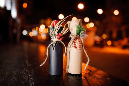 Two christmas decorated gift bottles standing on the wooden bench on the background of night street