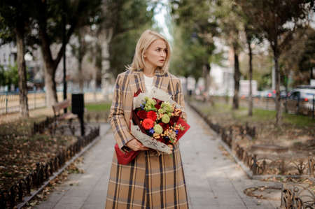Blonde woman in plaid coat holding a bright bouquet of flowers standing on alley in the park