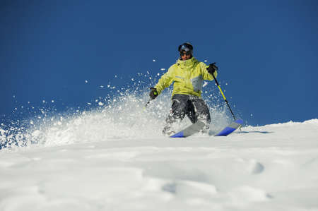 Young skier dressed in bright yellow sportswear riding down the mountain slope in Georgia, Gudauri on sunny day Stockfoto