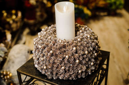 White burning Christmas candle in candlestick made of fir cones and little decorative white balls covered with artificial snow