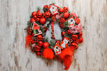 Christmas Wreath decorated with red balls, bows, roses and toy houses on the wooden background Stock Photo