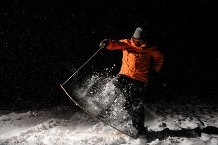 Active and young snowboarder dressed in orange sportswear and mask jumping on a snowy hill at night