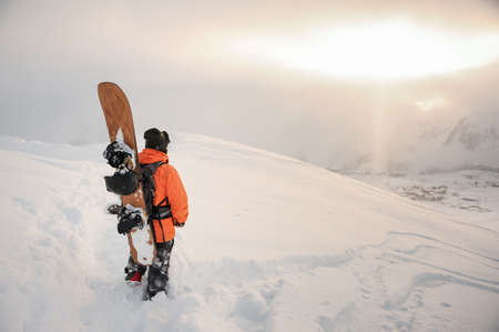 Rear view of professional snowboarder standing on the mountain peak with a board and looking at the sky