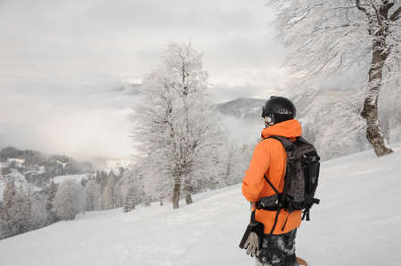 Man standing with the snowboard in the mountain and looking into a distance in the popular tourist resort in Goderzi, Georgia