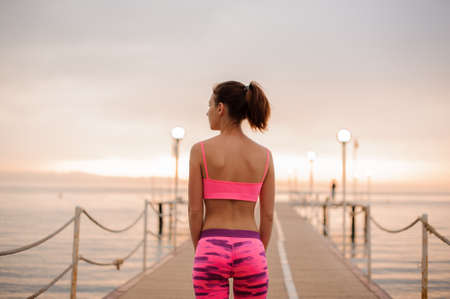 Girl standing near the sea on the bridge on the sunrise and watching to the side.Conception of the healthy lifestyle. 스톡 콘텐츠