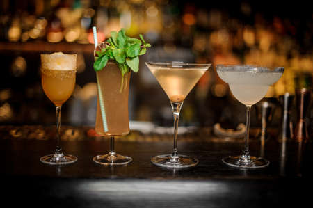 Set of classic cocktails: Dirty Martini, Sherry Cobbler, Brandy Crusta and Margarita arranged on the bar counter Stock Photo