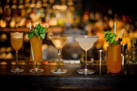Set klassischer Cocktails: Dirty Martini, Sherry Cobbler, Brandy Crusta, Margarita und Cobras Fang auf der Bartheke arrangiert
