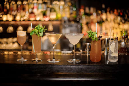 Set of classic cocktails: Dirty Martini, Sherry Cobbler, Brandy Crusta, Margarita, Cobras Fang and Tom Collins arranged on the bar counter