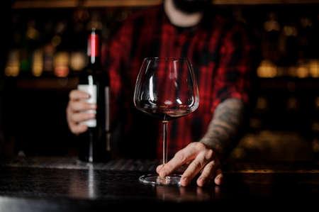 Barkeeper mit einem leeren Burgunya-Glas und einer Flasche Rotwein Standard-Bild