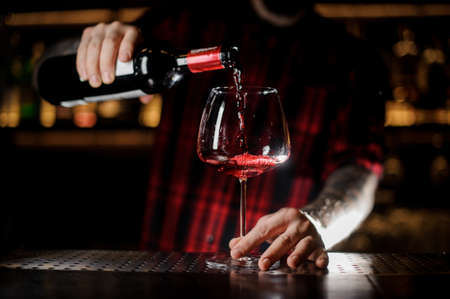 Tattooed barman pouring red wine into the burgunya glass