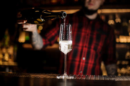 Barman pouring champagne into an elegant glass