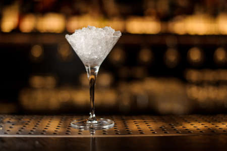 Elegant martini glass filled with ice on the bar