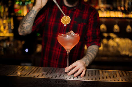 Bartender adding to a Sicilian Tonic cocktail in the glass one orange slice with tweezers on the bar counter 版權商用圖片 - 114129755