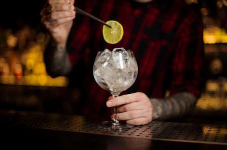 Camarero añadiendo una rodaja de limón con pinzas a la copa de cóctel llena de cubitos de hielo de pie sobre la barra de acero