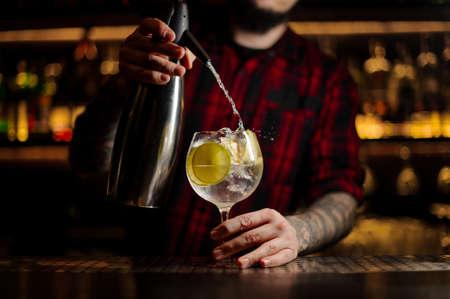 Barman ajoutant de l'eau tonique au verre à cocktail plein de glaçons avec des tranches de citron vert sur le comptoir du bar en acier