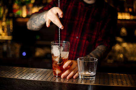 Barman stirring strong alcoholic cocktail with ice cubes on the bar counter using a professional spoon Reklamní fotografie
