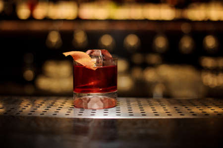 Glass of a Boulevardier cocktail with orange zest and ice cube on the steel wooden bar counter