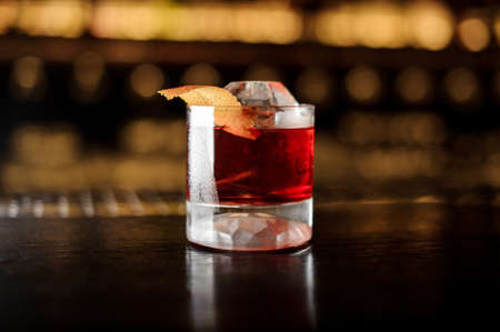Glass of a Boulevardier cocktail with orange zest on the steel and wood bar counter Banque d'images