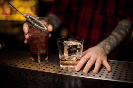 Bartender holding a glass of a Godfather cocktail and the measuring cup Stock Photo