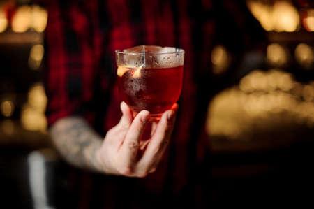 Professional bartender serving a glass of a Vieux Carre cocktail Standard-Bild - 114134308