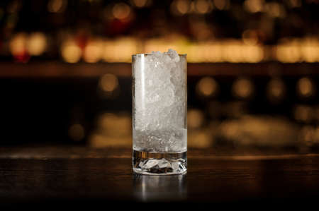 Glass of crushed ice standing on the empty bar counter Standard-Bild - 114134309