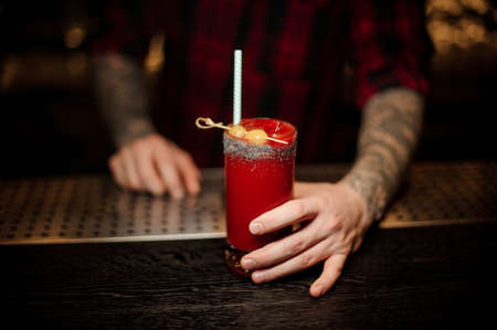 Bartender serving a Bloody Mary cocktail in the decorative glass with olives and tubule Standard-Bild - 114134315