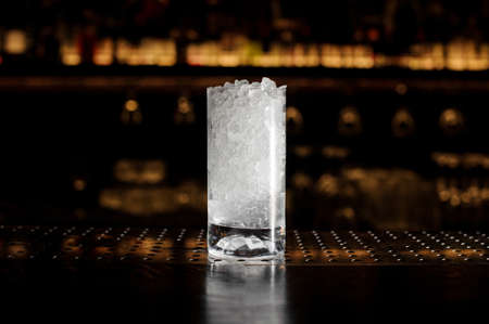 Glass of crushed ice standing on the empty bar stand Standard-Bild - 114134397