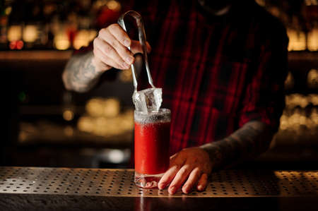 Bartender putting a big ice cube to a glass of a Bloody Mary cocktail Standard-Bild - 114134398