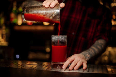 Bartender pouring a delicious Bloody Mary cocktail from the measuring cup Standard-Bild - 114134399