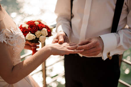 Broom putting on a golden wedding ring to a tender bride finger