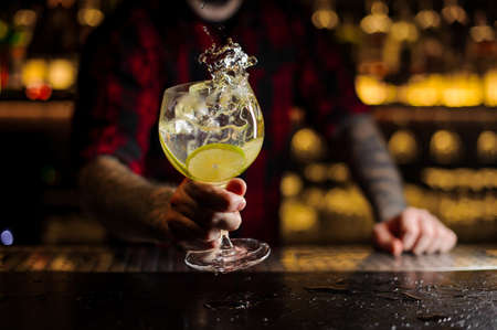 Barman with tattoos holding a glass of fresh sour and sweet citrus cocktail